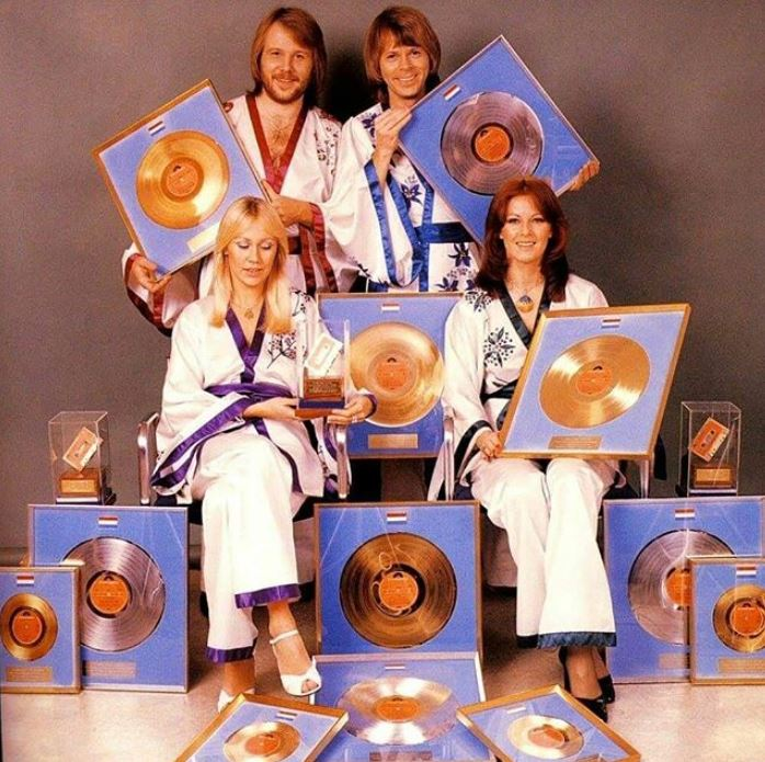 ABBA members with their records