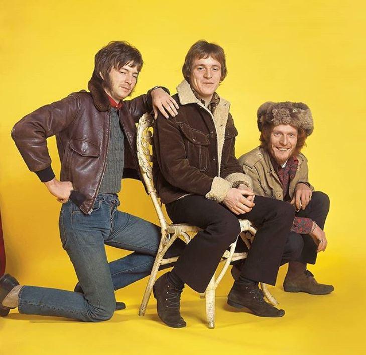 Cream rock band members smiling while posing.