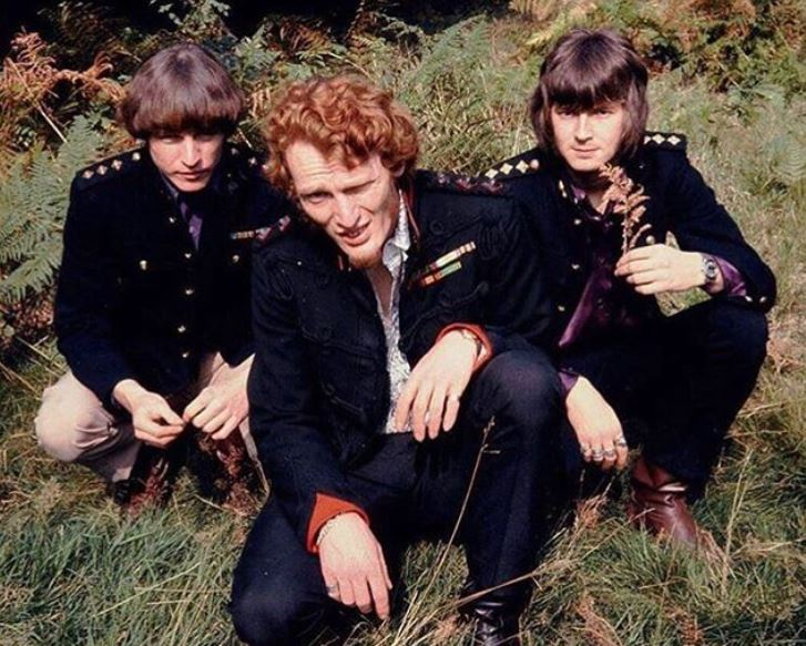 Cream members posing while in the grass.