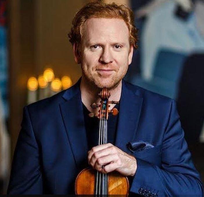 Daniel Hope holding his violin.