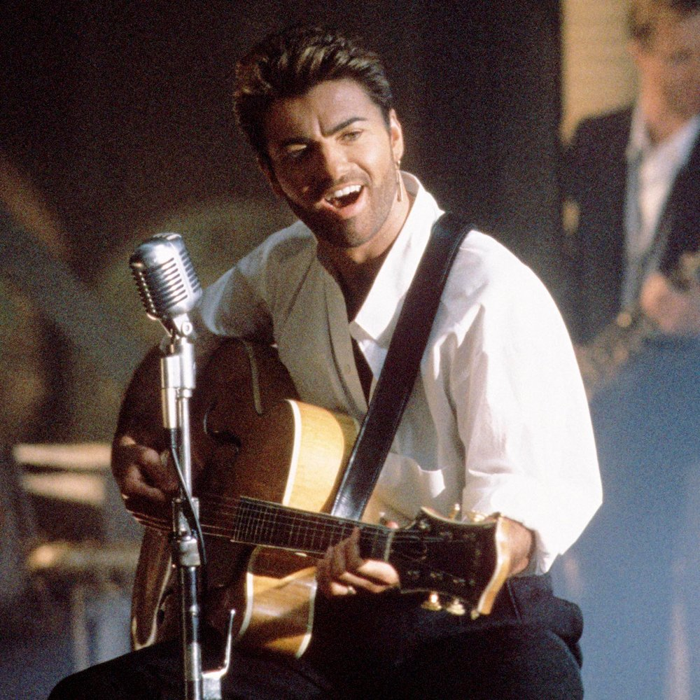 George Michael singing and playing his guitar