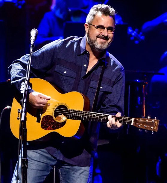 Vince Gill smiling while playing his guitar