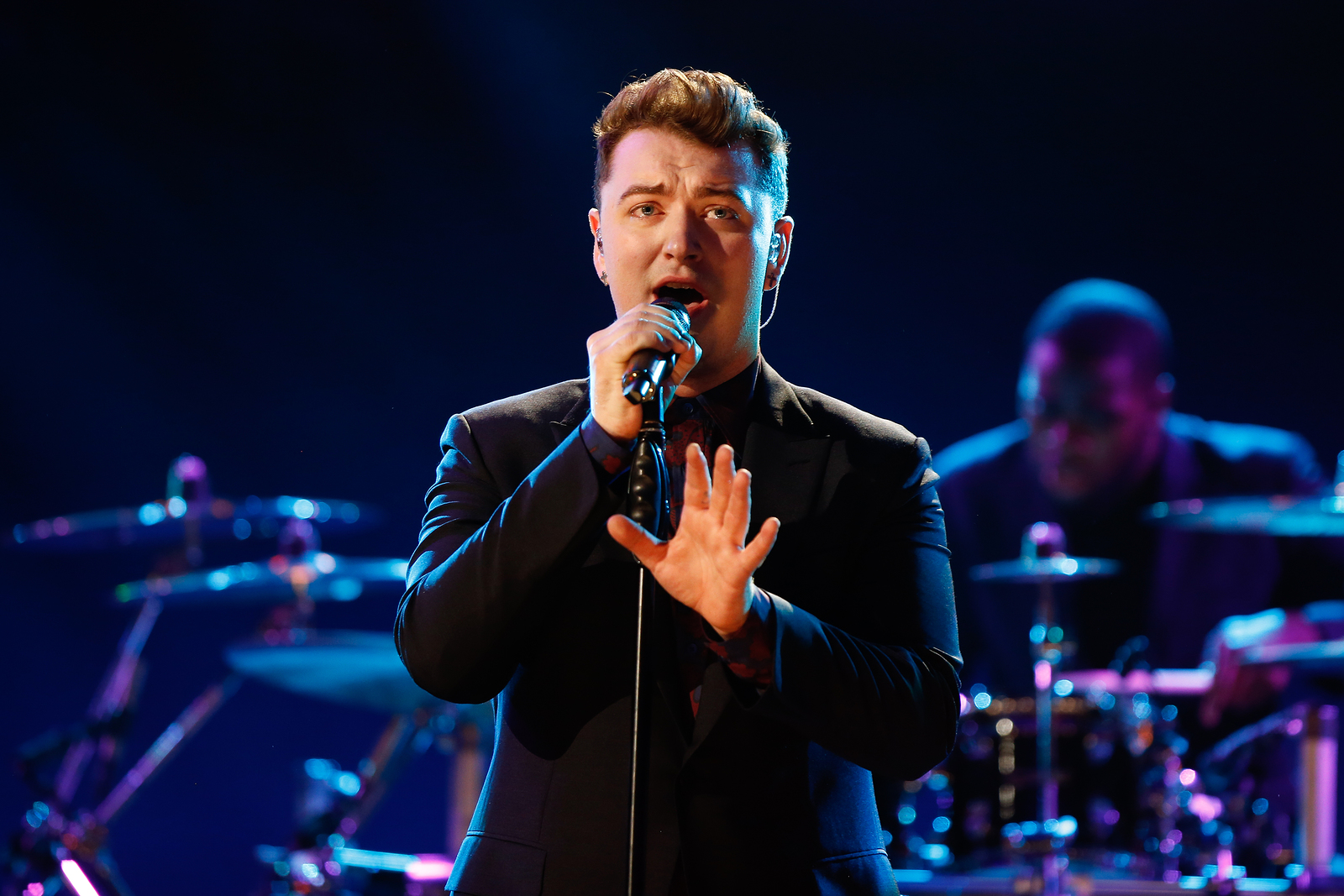 Singer Sam Smith performing on stage.